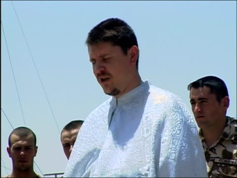 may 2004 medium shot priest giving mass with romanian soldiers standing behind him/ kandahar airfield afghanistan/ audio - operazione enduring freedom video stock e b–roll