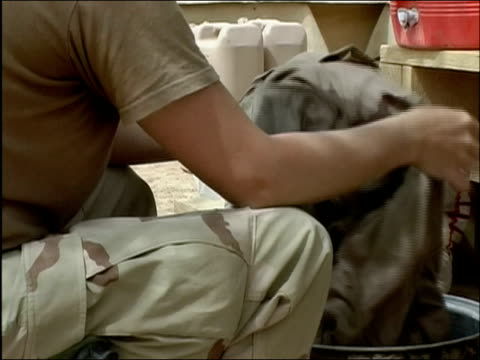 may 2004 medium shot soldier hand washing her fatigues in bucket / zoom in on her face / tarin kowt afghanistan / audio - water cooler stock videos & royalty-free footage