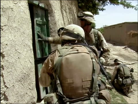 may 2004 medium shot two soldiers breaking green door down and entering building while other soldiers stand guard/ oruzgan province afghanistan/ audio - operazione enduring freedom video stock e b–roll