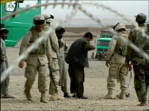 May 2004 Medium shot view through barbed wire fence of US troops patting down Afghan truck drivers at check point / Tarin Kowt Afghanistan / AUDIO