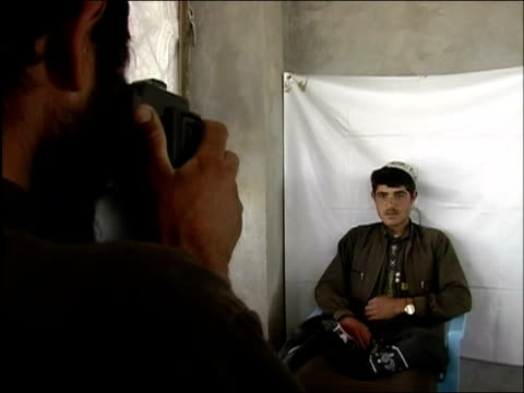 may 2004 medium shot young afghan man has photo taken for id in front of white sheet/ oruzgan province afghanistan/ audio - operazione enduring freedom video stock e b–roll