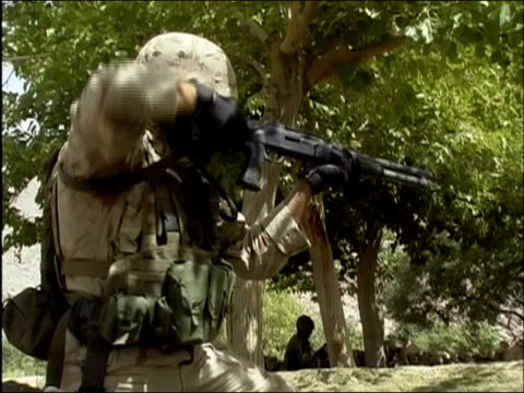 may 2004 medium shot zoom in us soldier preparing rifle and aiming / oruzgan province aghanistan / audio - operazione enduring freedom video stock e b–roll