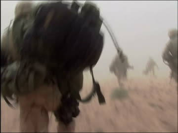 vidéos et rushes de may 2004 shaky long shot point of view us troops disembarking helicopter and running to take up positions / oruzgan province, aghanistan / audio - afghanistan