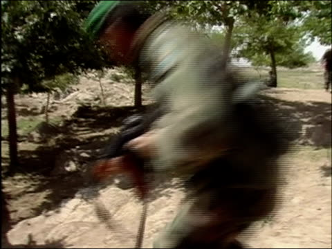 may 2004 shaky medium point of view shot afghan national army soldiers running through opening in wall holding machine guns / oruzgan province... - afghan national army stock videos & royalty-free footage