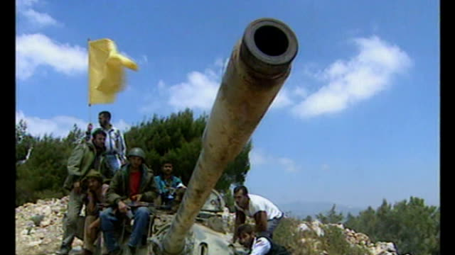 t24050005 / may 2004 group of hizbollah guerrillas standing on top of captured southern lebanese army tank waving flags barrel of seized tank... - hezbollah stock videos & royalty-free footage
