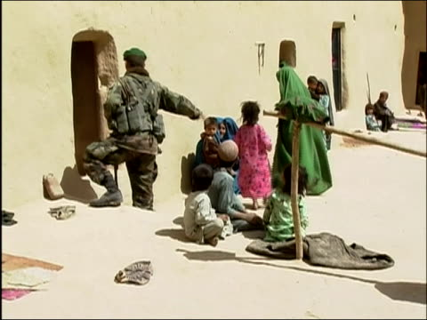may 2004 wide shot afghan national army soldier directing women and children out of building / oruzgan province aghanistan / audio - operazione enduring freedom video stock e b–roll