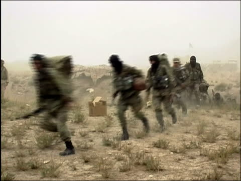 may 2004 wide shot afghan national army soldiers carrying machine guns and running in a line / oruzgan province aghanistan / audio - operazione enduring freedom video stock e b–roll
