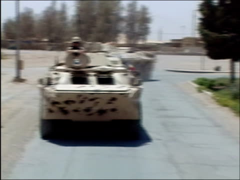 may 2004 wide shot armoured vehicle drives toward camera as two more turn onto road behind it/ kandahar afghanistan/ audio - heckklappe teil eines fahrzeugs stock-videos und b-roll-filmmaterial