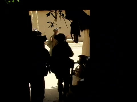 may 2004 wide shot four us soldiers pass through dark passage to sunlit courtyard/ two afghan men putting their arms up/ oruzgan province,... - menschliche gliedmaßen stock-videos und b-roll-filmmaterial