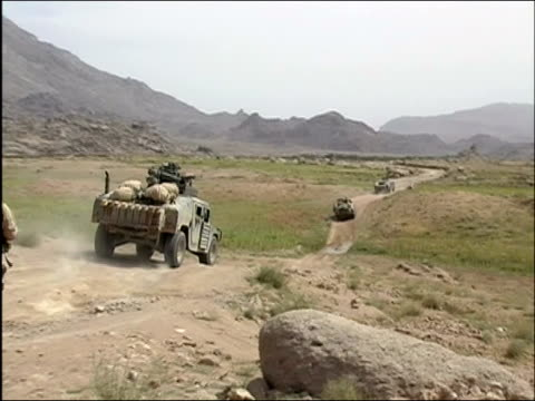 stockvideo's en b-roll-footage met may 2004 wide shot military humvees riding along dirt road / us troops following on foot / oruzgan province aghanistan / audio - humvee
