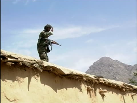 may 2004 wide shot zoom in afghan national army soldier standing on roof of building and holding machine gun / oruzgan province aghanistan / audio - operazione enduring freedom video stock e b–roll
