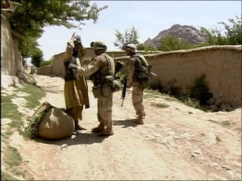 may 2004 wide shot zoom in us soldiers searching afghan man on dirt road/ oruzgan province afghanistan/ audio - operazione enduring freedom video stock e b–roll