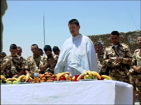 may 2004 wide shot zoom out priest conducting mass over table of fruit as romanian soldiers stand around/ kandahar airfield afghanistan/ audio - arms crossed stock videos & royalty-free footage