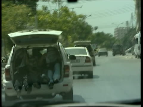 stockvideo's en b-roll-footage met may 2007 montage driver's pov following fatah supporters sitting in open trunk of car in front during conflict between hamas and fatah/ nablus... - passagiersstoel