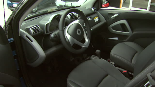 may 21, 2008 salesman showing interior and exterior of microcar to customer on dealership lot / arlington, virginia, united states - car interior stock videos & royalty-free footage