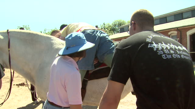 may 21 2009 ts therapist helping amputee off horse at fort myer rehabilitation clinic / arlington virginia united states - fort myer stock videos and b-roll footage