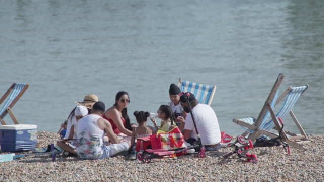 may 21. a family enjoys a picnic on brighton beach on the hottest day of the year so far on may 21, 2020 in east sussex, england. the uk has eased... - picnic stock videos & royalty-free footage