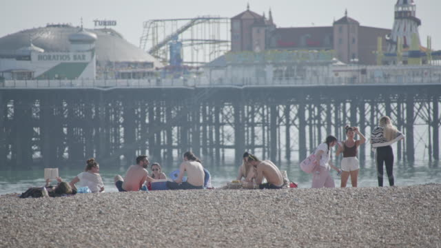 a group of young people enjoy brighton's shingle beach on the hottest day of the year so far on may 21 2020 in east sussex england the uk has eased... - young adult stock videos & royalty-free footage