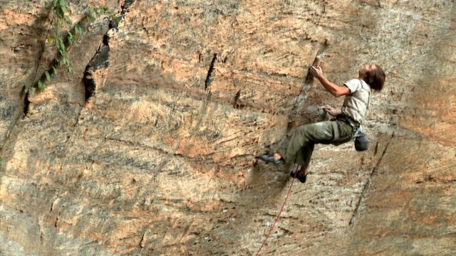 may 22, 2009 montage a climber losing his hold while free climbing a rock wall - カラビナ点の映像素材/bロール