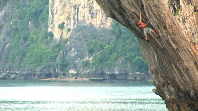 may 22 2009 montage a professional rock climber deep water soloing a limestone rock wall and then jumping into the clear water below with the rescue... - crimped hair stock videos and b-roll footage