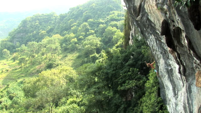 may 22, 2009 montage a professional rock climber free climbing a limestone rock wall in the jungle - free climbing stock-videos und b-roll-filmmaterial