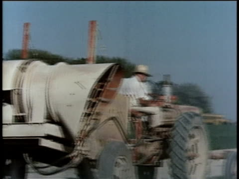 may 27, 1963 ws farmer wearing straw hat sprays crops with pesticide from tractor / united states - crop sprayer stock videos and b-roll footage