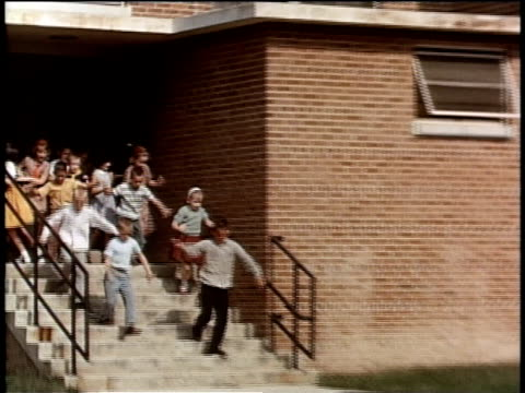 May 27, 1963 WS Large group of children run out of school doors onto front lawn / United States