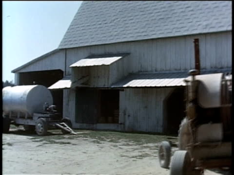 may 27, 1963 ws man drives tractor up to barn / united states - barn stock videos & royalty-free footage