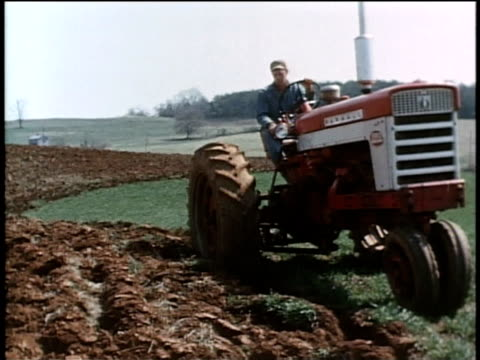 stockvideo's en b-roll-footage met may 27, 1963 ws man riding tractor plows his field to expose pests to the elements and to predators / united states - agrarisch beroep
