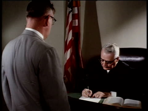 vídeos de stock, filmes e b-roll de may 27, 1963 montage a man signs a federal court order instructing a united states marshal to seize the food / united states - prédio federal