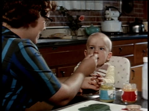 May 27, 1963 MS Mother spoons baby food into her baby's mouth / United States
