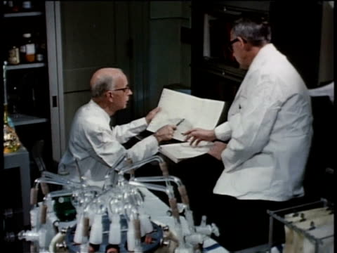 May 27, 1963 MS Two scientists analyze and discuss data from a piece of paper / United States