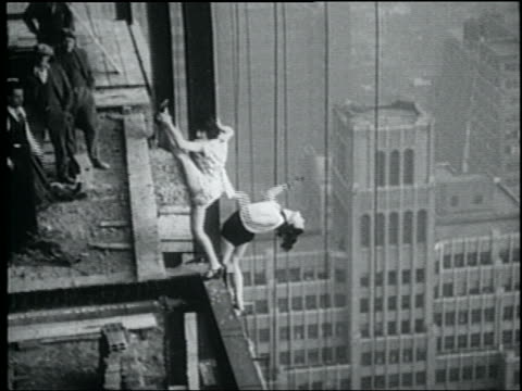 b/w may 28, 1930 2 women doing ballet stretches on edge of building under construction high above city - dehnen stock-videos und b-roll-filmmaterial