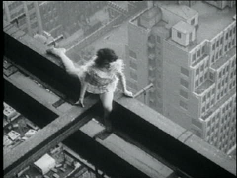 b/w may 28, 1930 high angle woman doing splits on iron girder high above city / waves + crawls away - 1930 stock-videos und b-roll-filmmaterial