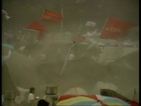 may 31 1989 film montage ws dust storm in student protestor encampment in tiananmen square/ ws crowd in front of gate of heavenly peace/ ms protestor... - anno 1989 video stock e b–roll