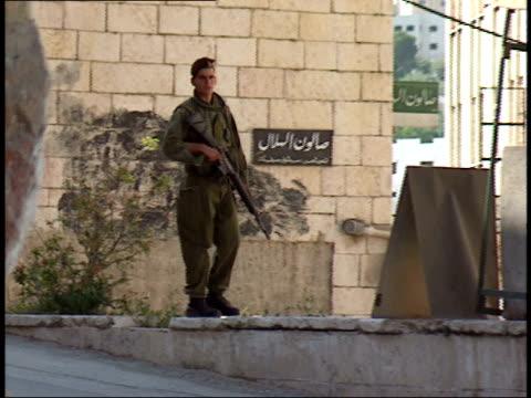 may 31, 1992 armed soldier walking up stone bank and platform to a shaded post station then sitting down / israel - e post bildbanksvideor och videomaterial från bakom kulisserna