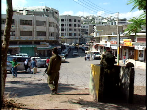 vidéos et rushes de may 31, 1992 armed soldiers looking out on busy city street sectioned off with coils of barbed wire / israel - soldat