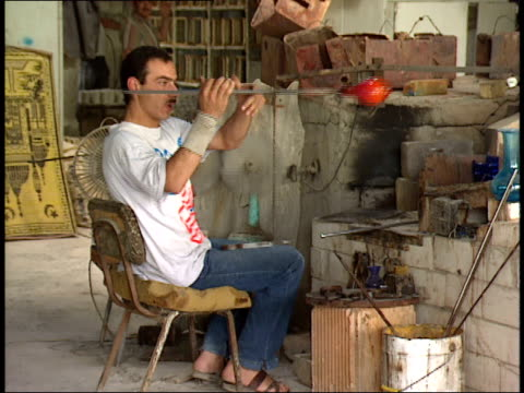 may 31 1992 swish pan artisans blowing glass in factory / israel - swish pan stock videos & royalty-free footage