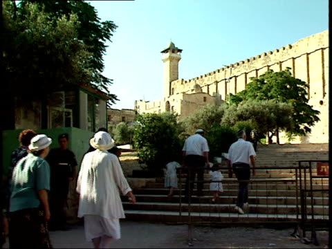 may 31, 1992 family walking to the western wall with the minaret of al-aqsa mosque overhead / jerusalem, israel - gerusalemme est video stock e b–roll