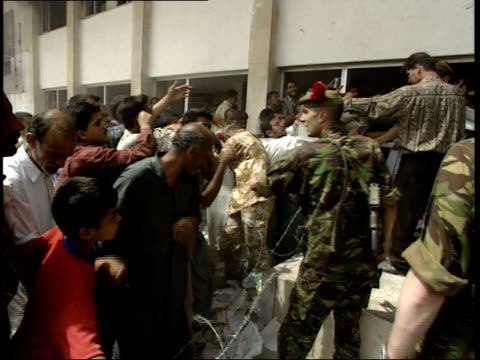 may 7, 1999 british army soldiers overseeing the distribution of newspapers to a crowd as a boy is caught by concertina wire barricade / basra, iraq - barricade stock videos & royalty-free footage