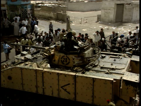 may 7, 1999 british army tank, land rover, and soldiers monitoring a chaotic street crowd / basra, iraq - basra stock-videos und b-roll-filmmaterial