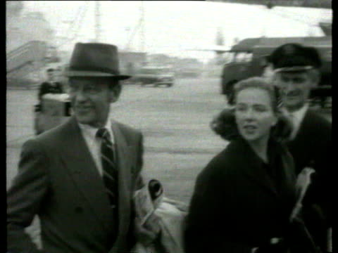 vídeos de stock e filmes b-roll de may 8 1956 film montage ms fred astaire and daughter ava walking at airport/ ws astaire and daughter waving before getting on air france plane/ europe - fato completo