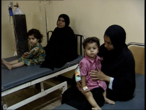 may 8, 1999 children's hospital ward with mother holding her toddler prior to examination / basra, iraq - basra点の映像素材/bロール