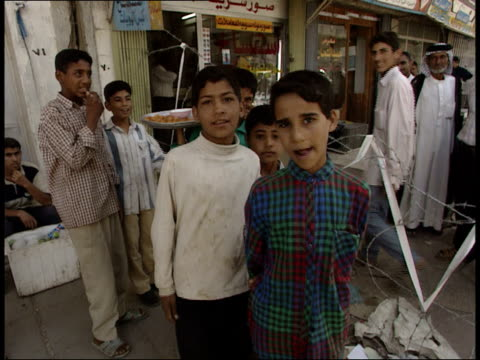 may 8, 1999 montage pedestrians on the sidewalk pose for the cameras / basra, iraq - basra stock-videos und b-roll-filmmaterial