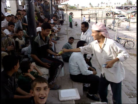 May 8 1999 PAN Vendor selling food to fans in the pavilion during soccer game / Basra Iraq