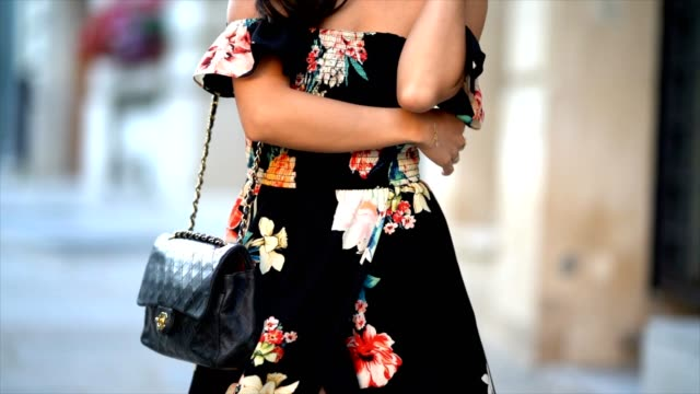 may berthelot fashion blogger and head of legal at videdressingcom wears a new look offshoulder long floral print black dress a chanel bag and hm... - black dress stock videos & royalty-free footage