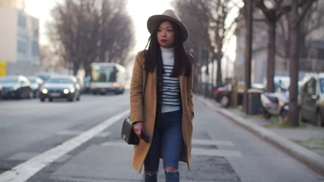 may berthelot, fashion blogger, is wearing a hat, a camel coat, a chanel boy bag with a pompom, blue denim jeans, and brown suede boots, outside the... - jeans stock videos & royalty-free footage