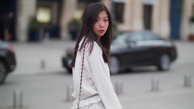 may berthelot, head of legal at videdressing.com and fashion blogger, wears a magali pascal white lace blouse top, chanel jeans, valentino tango... - ブラウス点の映像素材/bロール