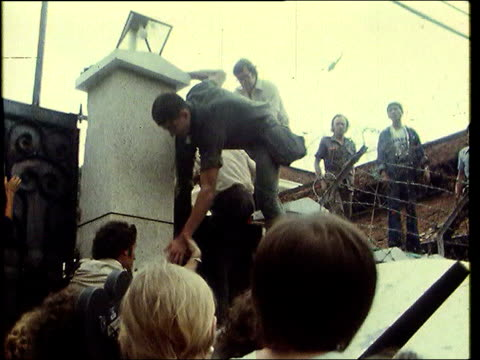 may in 1975 saigon was evacuated saigon ext south vietnamese soldier carrying wounded child / crowd of south vietnamese people climbing wall into us... - south vietnam stock videos and b-roll footage