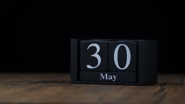 stockvideo's en b-roll-footage met mei maand kalender 4k stop beweging snel tempo van de tijd tijdens de maand door handgemaakte houten kalender met datum maand en dag op een houten tafel - mei